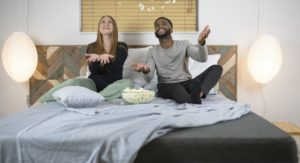 Man and woman sitting on a CouchBed
