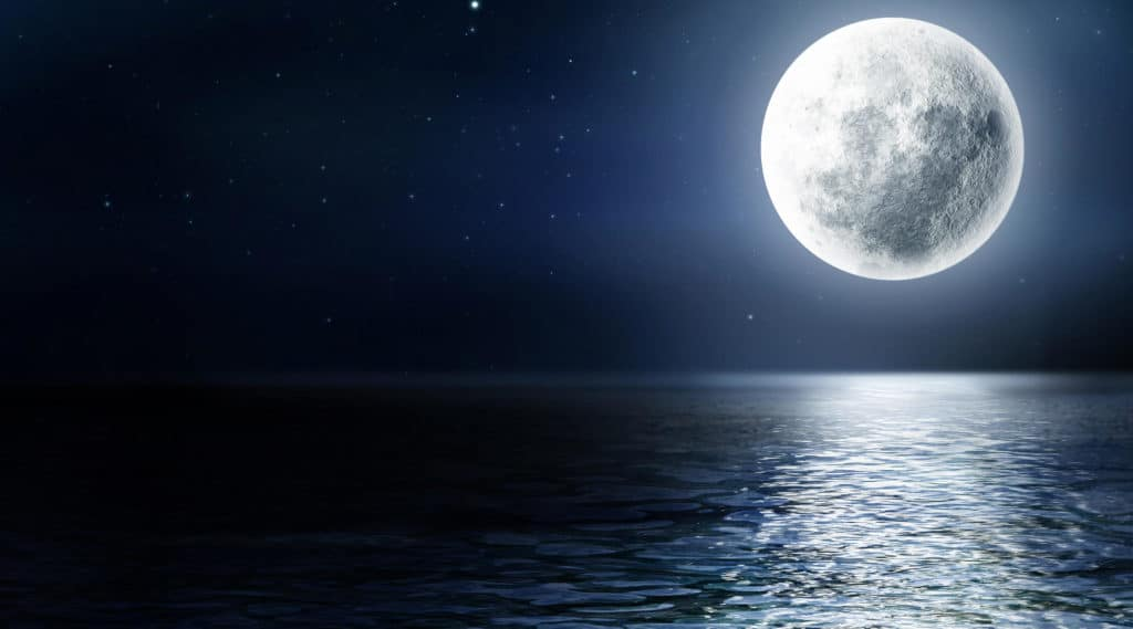 Full moon over a body of water