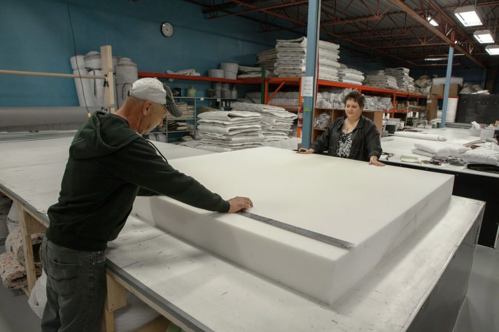Workers measuring foam at a mattress factory.