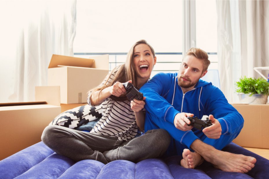 couple on air bed playing video games