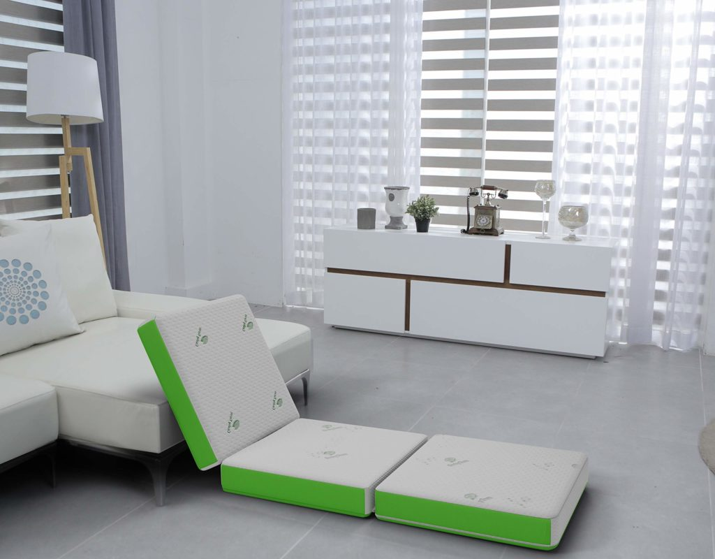 green and white folding mattress in a living room