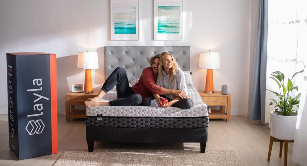 couple sitting on layla memory foam mattress